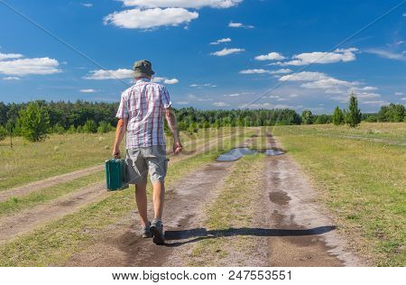 Mature Man Walking On A Summer Country Road With Green Suitcase