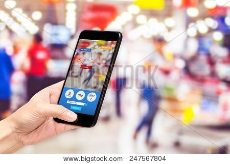 Hand Hold Mobile Phone And Using Augmented Reality ( Ar ) App For See Promotion Sale In Supermarket