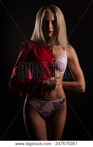 Girl In Black Underwear And A Red Jacket Stands On Dark Background. Low Key Light