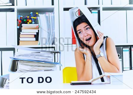 Funny Overworked Girl With A Folder On Her Head Sitting In The Workplace Cluttered With Folders. Rea