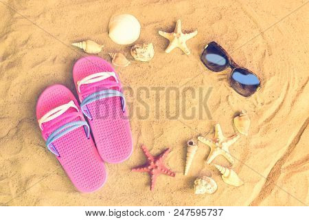 Pink Flip Fops, Sunglasses, Starfishes And Seashells On Sand Beach