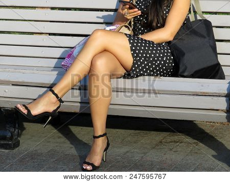 Woman In A Short Dress And Black Sandals With High Heels Sitting With A Smartphone In Her Hand On Th