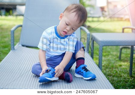 Cute Little Asian 18 Months / 1 Year Old Toddler Boy Child Sitting And Concentrate On Putting On His