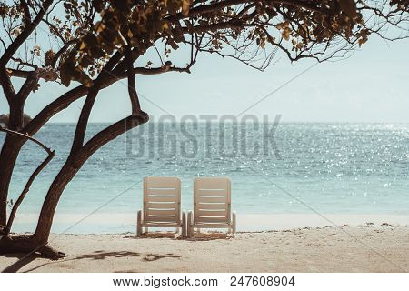 Two Chaise-lounges On The Coral Sand Beach Under The Tree With A Summer Idyllic Seascape Behind; Emp