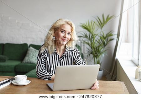 Positive Cheerful Mature Female In Her Sixties Doing Finances Online, Sitting At Desk In Front Of Op