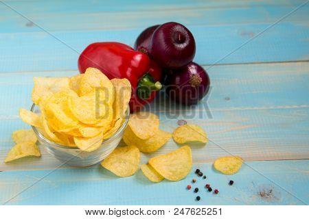 Hot Spicy  Potato Chips Ready To Eat. Crispy Potato Chips In A Glass Bowl With Paprika And Onions On