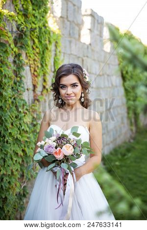 Beautiful Young Bride With A Bouquet Of Wedding Flowers. Holiday Dress A