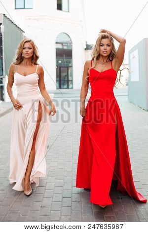 Two Fashionable And Gorgeous Girls Wearing Elegant Evening Dresses. Slender Attractive Women With Bl
