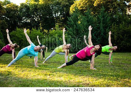 Group Of Adult Women Attending A Yoga Class Outdoors, Triangle Pose