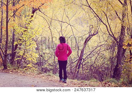 Person Posing For Aphoto In A Forest Of Autumn Foliage In Arrowtown New Zealand