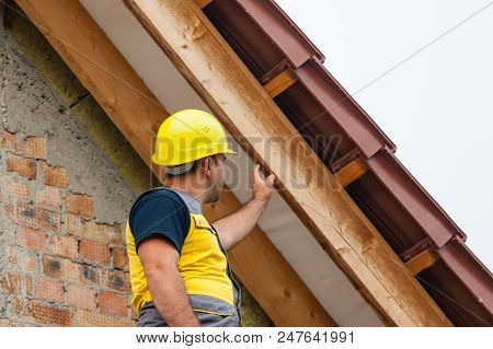 The Builder Dressed In Special Clothing Checks The Roof Supports