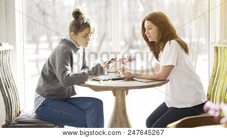 Two Female Friends Busy Sitting In A Cafe Face To Face Holding A Phone Taking Notes Having Serious M