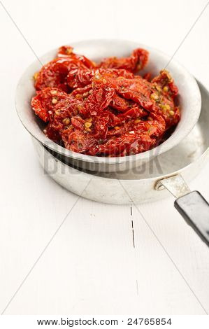sun-dried tomatoes with olive oil in an old tinware, white wooden background