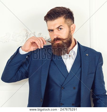 Portrait Of Serious Fashionable Handsome Man In Blue Suit. Brutal Bearded Man In Suit Looking At The