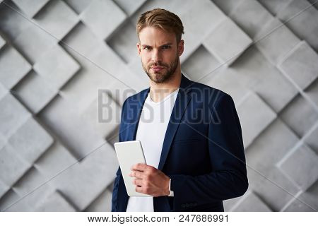 Waist Up Portrait Of Earnest Man Standing With Tablet In Hand. He Is Gazing Forward With Solemn And
