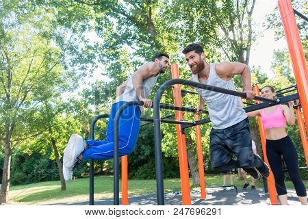 Two strong and motivated young men doing dips exercise for the upper body, during challenging workout with their friend in an outdoor fitness park with modern equipment