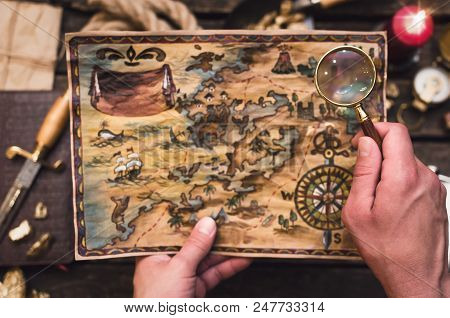 Treasure Map In Treasure Hunter Hands. Pirate Man Learning An Old Map With Red Mark.