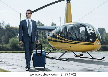 Ready To Depart. Upbeat Young Ceo Arriving At A Heliport And Carrying His Suitcase While Smiling Con