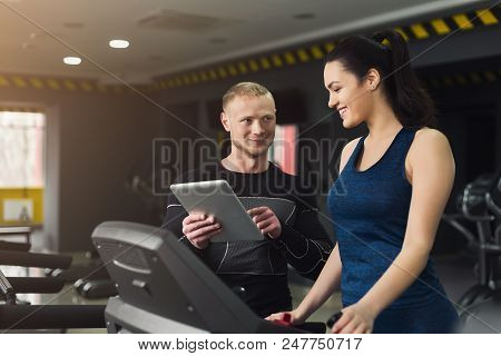 Fitness instructor helps young woman on elliptical trainer. Coach discussing workout plan with girl on treadmill. Cardio workout in gym, healthy lifestyle, copy space poster