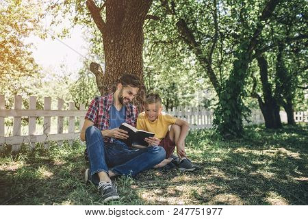 Careful An Good Father Is Sitting With His Son Inder Tree And Holding Book. They Are Looking At It.