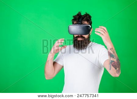Man With Beard In Vr Glasses, Green Background. Hipster On Busy Face Exploring Virtual Reality With