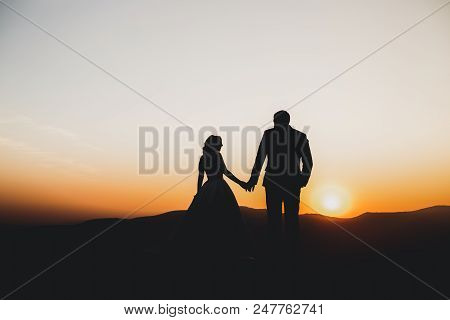 Happy Beautiful Wedding Couple Bride And Groom At Wedding Day Outdoors On The Mountains Rock. Happy