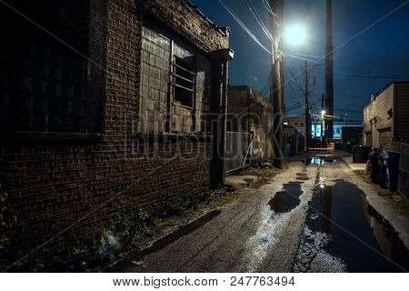 Dark, gritty and wet industrial city alley at night after rain