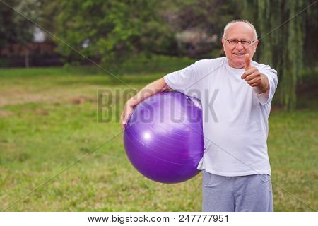 Thumb Up For Healthy Exercising - Happy Senior Man With Fitness Balls In Park And Exercising