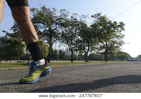 Detail Of Leg Of A Street Runner, Leaving The Image With Background Of Trees And Sky