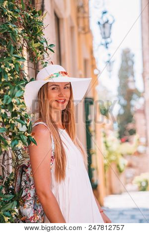 Beautiful Girl In A Shite Dress And Summer Hat Exploring The Old Town Of Taormina On Sicily Island.