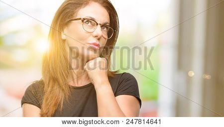 Middle age woman wearing black shirt and glasses thinking and looking up expressing doubt and wonder