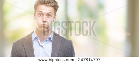 Young handsome blond business man puffing cheeks with funny face. Mouth inflated with air, crazy expression.