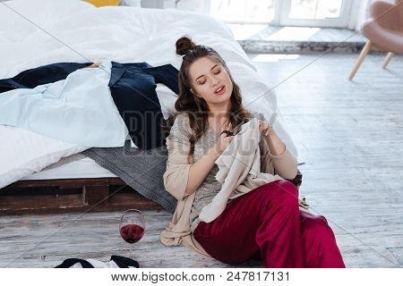 Ex Wife. Ex Wife Sitting On The Floor Near Bed With Scissors While Cutting Many Clothes After Drinki