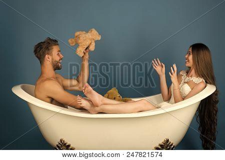 Married Couple Having Fun. Boyfriend And Girlfriend Relax On Blue Background. Man In Bathtub Near Gi