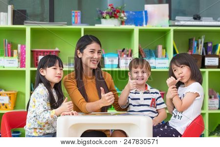 Asian Female Teacher And Mixed Race Kids Thumbs Up In Classroom,kindergarten Pre School Concept