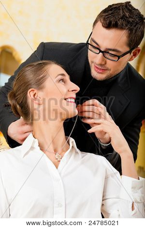 Man giving his wife a necklace as a gift