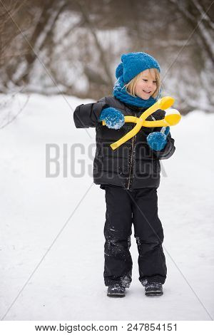 Portrait Of Adorable Little Kid Boy With Long Blond Hair Making Snowballs Outdoors. Child With Blue