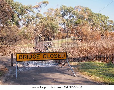 Remains Of A Burned Down Foot Bridge And A Warning Sign After Bush Fire In An Suburban Area Of Knox