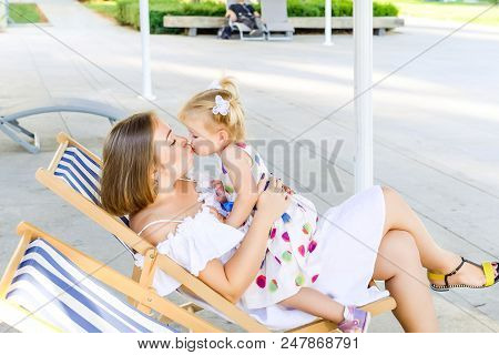 Happy Mother And Daughter Kissing Each Other During Relaxing In The Deckchair In The City Park Recre
