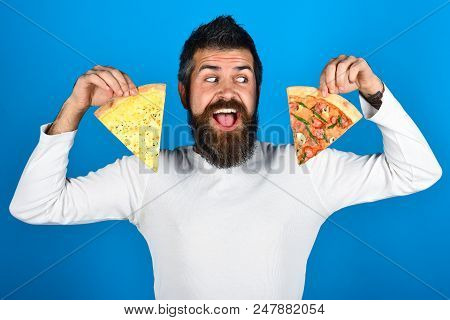 Bearded Man Holds Two Pieces Of Pizza In His Hands. Happy Hungry Man Eating Pizza. Handsome Man With
