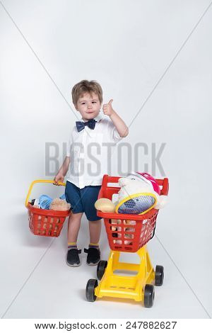 Shopping Concept - Child With Shopping Basket And Shopping Cart Giving Thumb Up. Toddler Boy With Ch