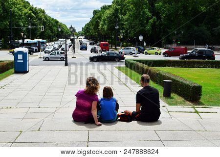 Family -  Mom, Dad And Child Sitting On Large Grey Concrete Plate Stairs Relax And Enjoy View Of Cit