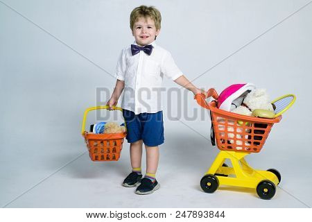 Shopping, Discount, Sale Concept - Cheerful Little Boy With Shopping Cart And Basket. Kid Plays In S