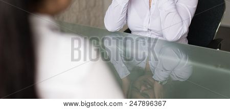 Woman Crying After Fired From Job At Office In Glass Table Reflection