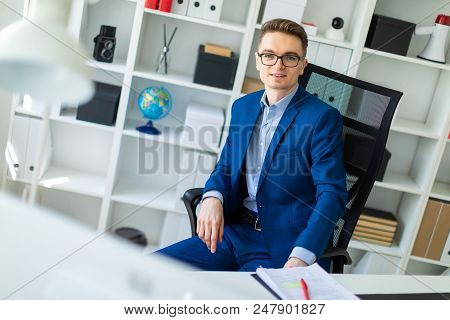 A Handsome Young Man With Glasses, A Blue Suit And A Light Shirt Is Working In The Office. Photo Wit