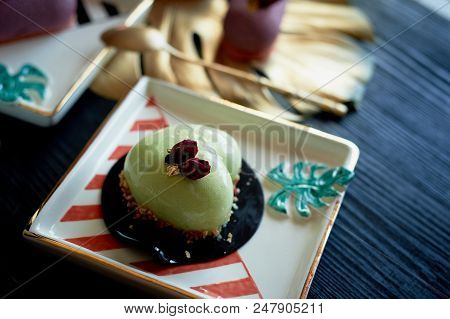 Pistachio mousse cake in the fishing Culinary art. On striped graphic saucers poster