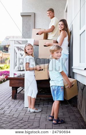 Family with boxes going to the house