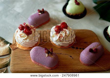 Purple fruit mousse cake, meringue Anna Pavlova on a wooden Board. Culinary art poster