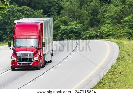 A Red Semi Crests A Hill On An Interstate.  The Truck Is Placed In The Image So A Great Deal Of Copy