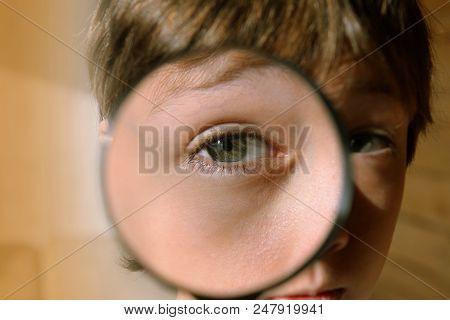 Eye Through A Magnifying Glass. Look Through The Magnifier. The Child Looks Through A Magnifying Gla